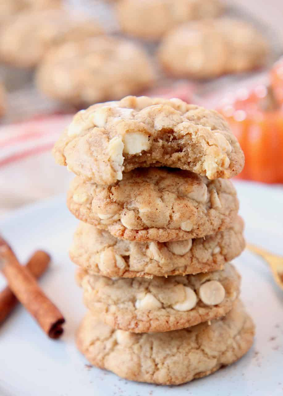 Stacked up pumpkin spice cookies on plate with cinnamon sticks