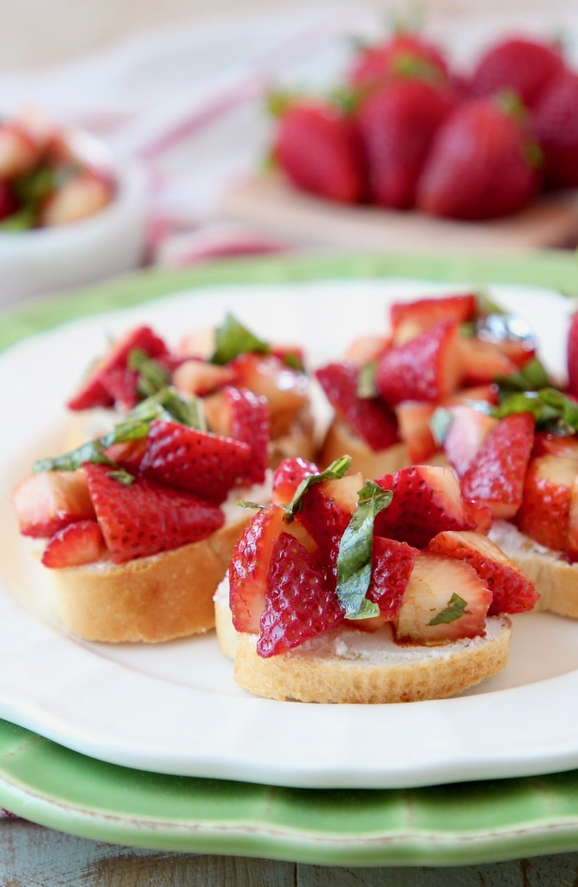 Diced strawberries and basil on top of baguette slices on a white plate