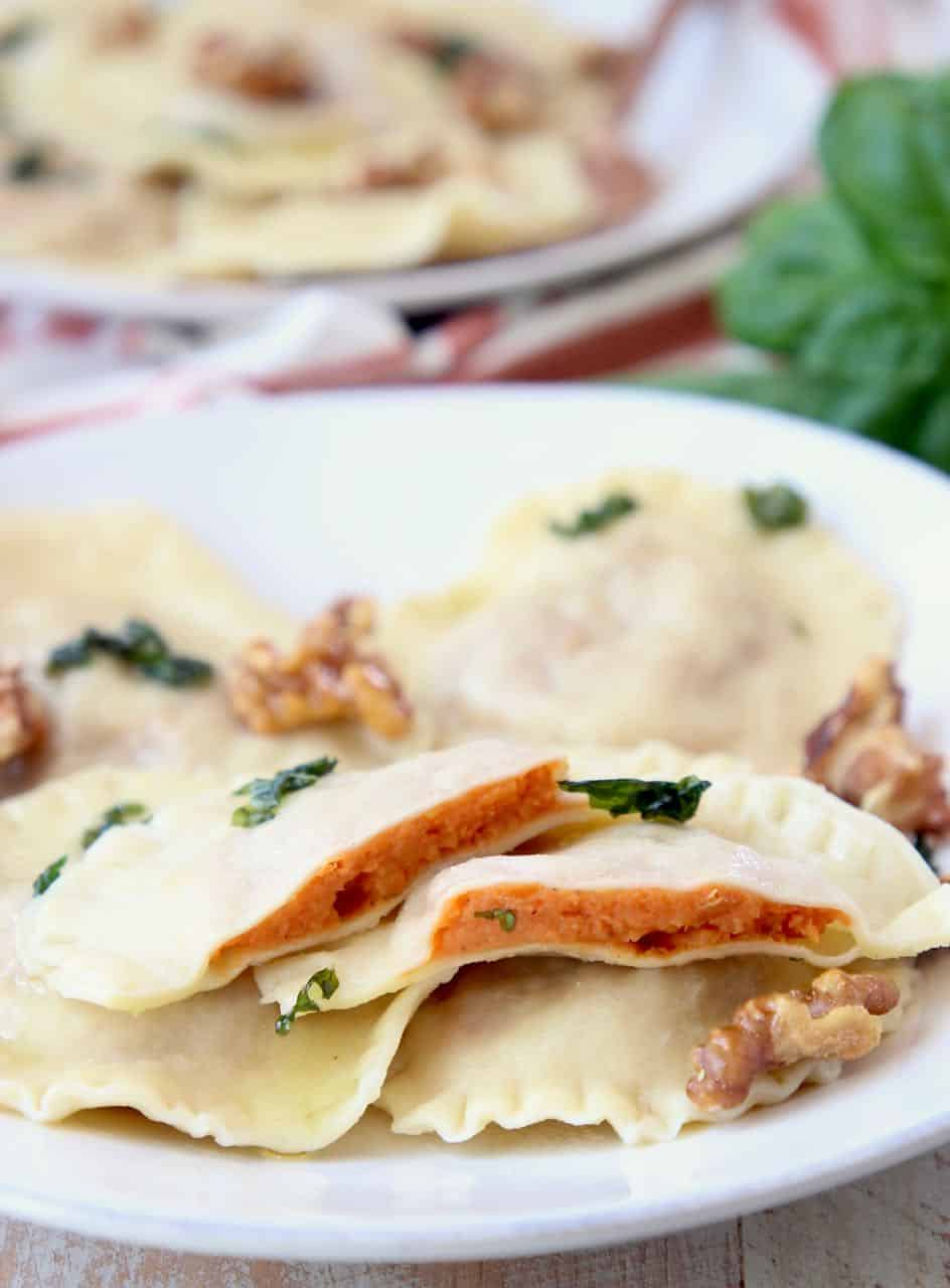 Sweet potato ravioli sliced in half on plate with whole raviolis and walnuts