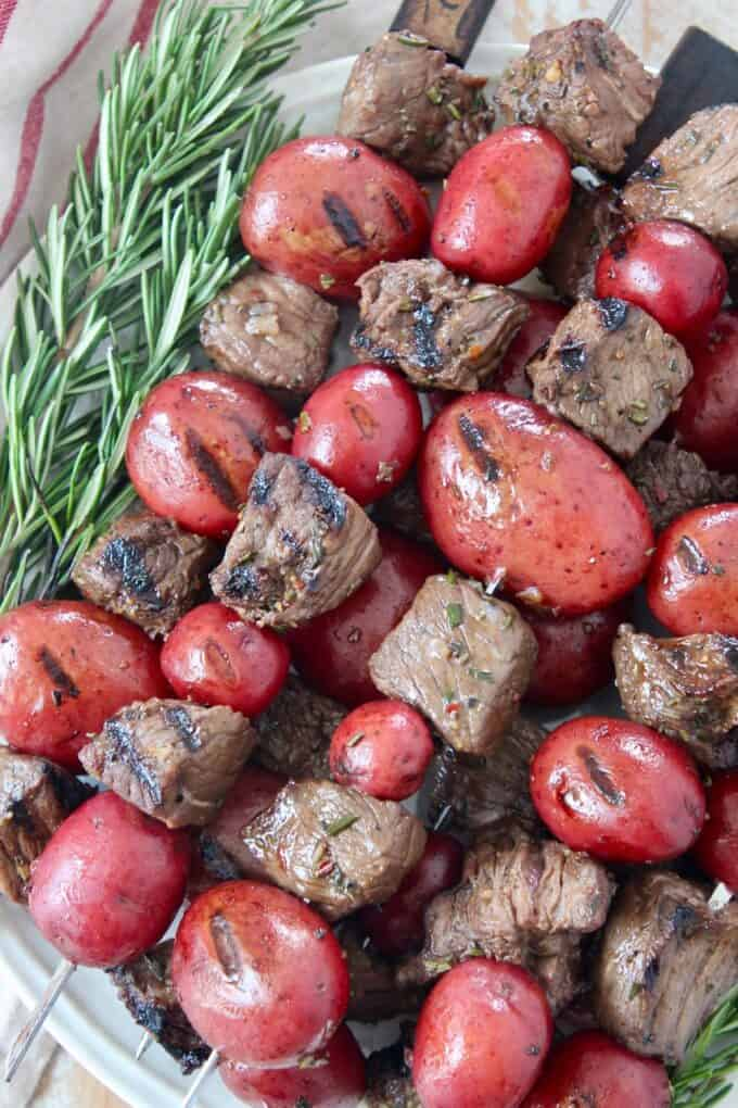 pieces of steak and baby potatoes on skewers stacked up on plate