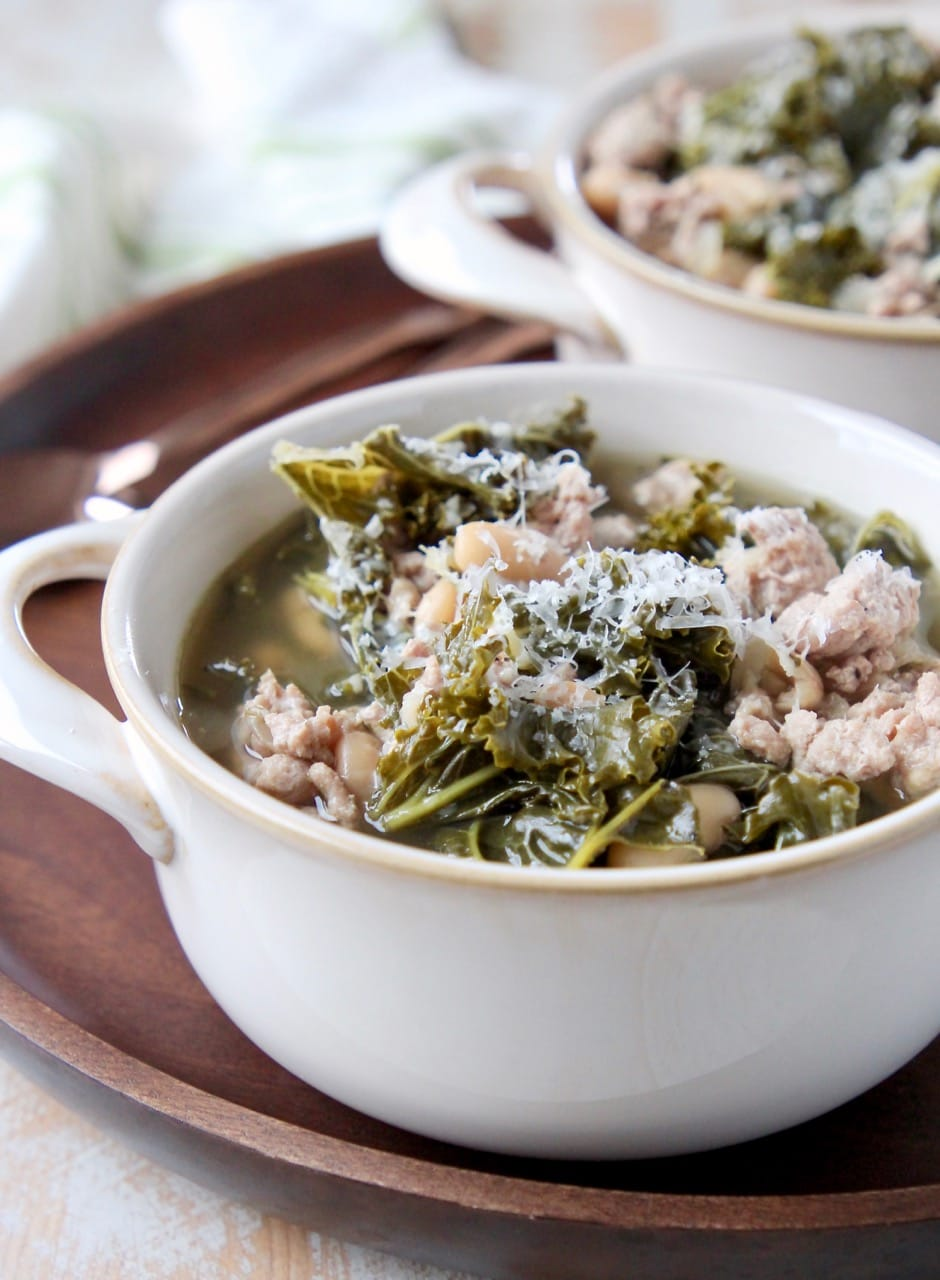 Ground turkey and kale soup in white soup crock on wood tray