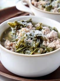 Kale turkey soup in white soup crock on dark wood tray