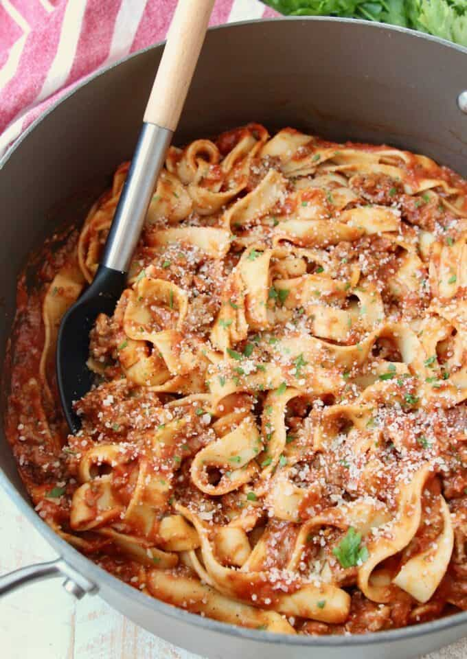 pasta tossed in tomato meat sauce in large pot with serving spoon