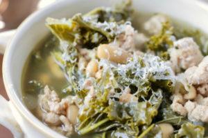 Kale turkey soup in white bowl on wood tray