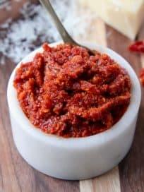 Sun dried tomato pesto in small white bowl on wood cutting board