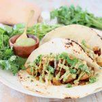 Butternut Squash tacos with creamy avocado sauce and fresh cilantro on flour tortillas