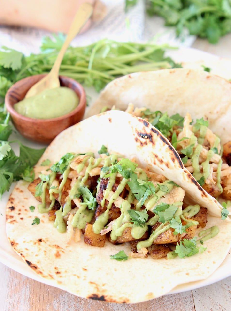 Butternut squash tacos on flour tortillas with creamy avocado sauce and fresh cilantro