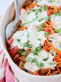 Italian casserole with sweet potato noodles and mozzarella cheese in oval white baking dish