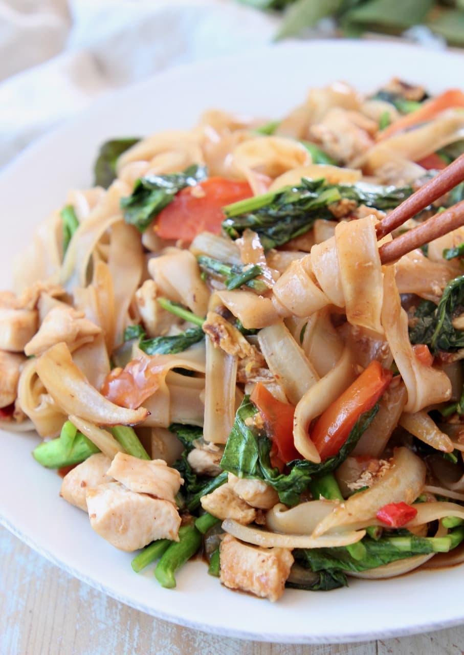 Drunken noodles, twirled around chopsticks on white plate