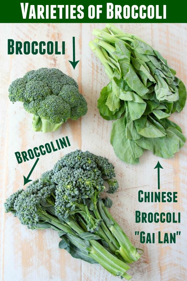 Broccoli, Chinese broccoli and broccolini displayed on white cutting board