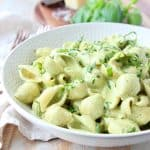 Creamy pesto pasta in white bowl with fresh basil on top