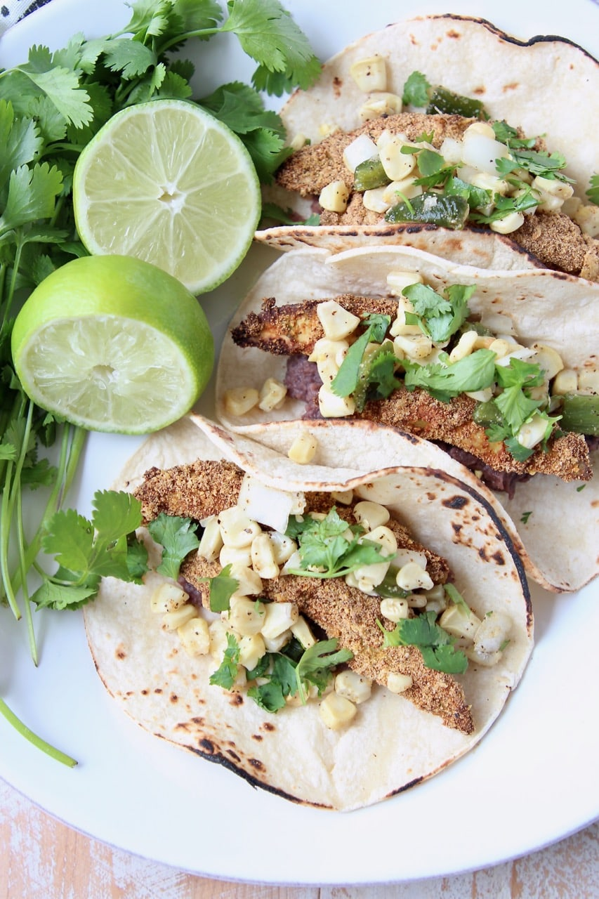 Overhead shot of crispy baked avocado tacos in corn tortillas on white plate with lime wedges