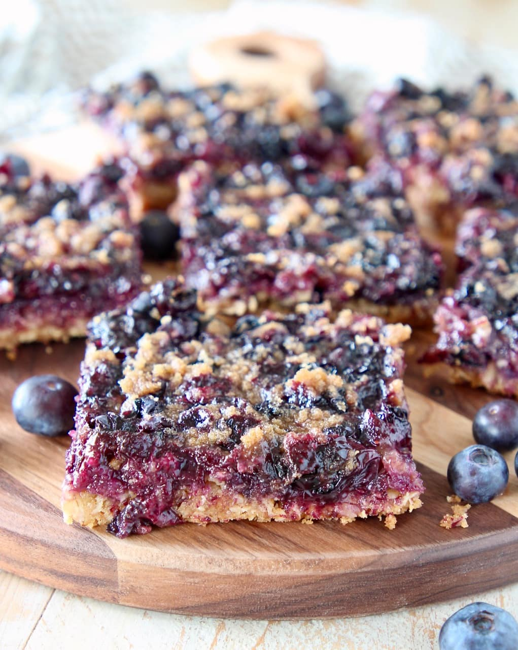 Blueberry oatmeal bars cut into squares, sitting on wood cutting board with fresh blueberries