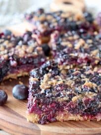 Blueberry oat bars, sliced into squares on a wood cutting board