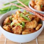 Orange chicken in bowl with scallions and wood chopsticks