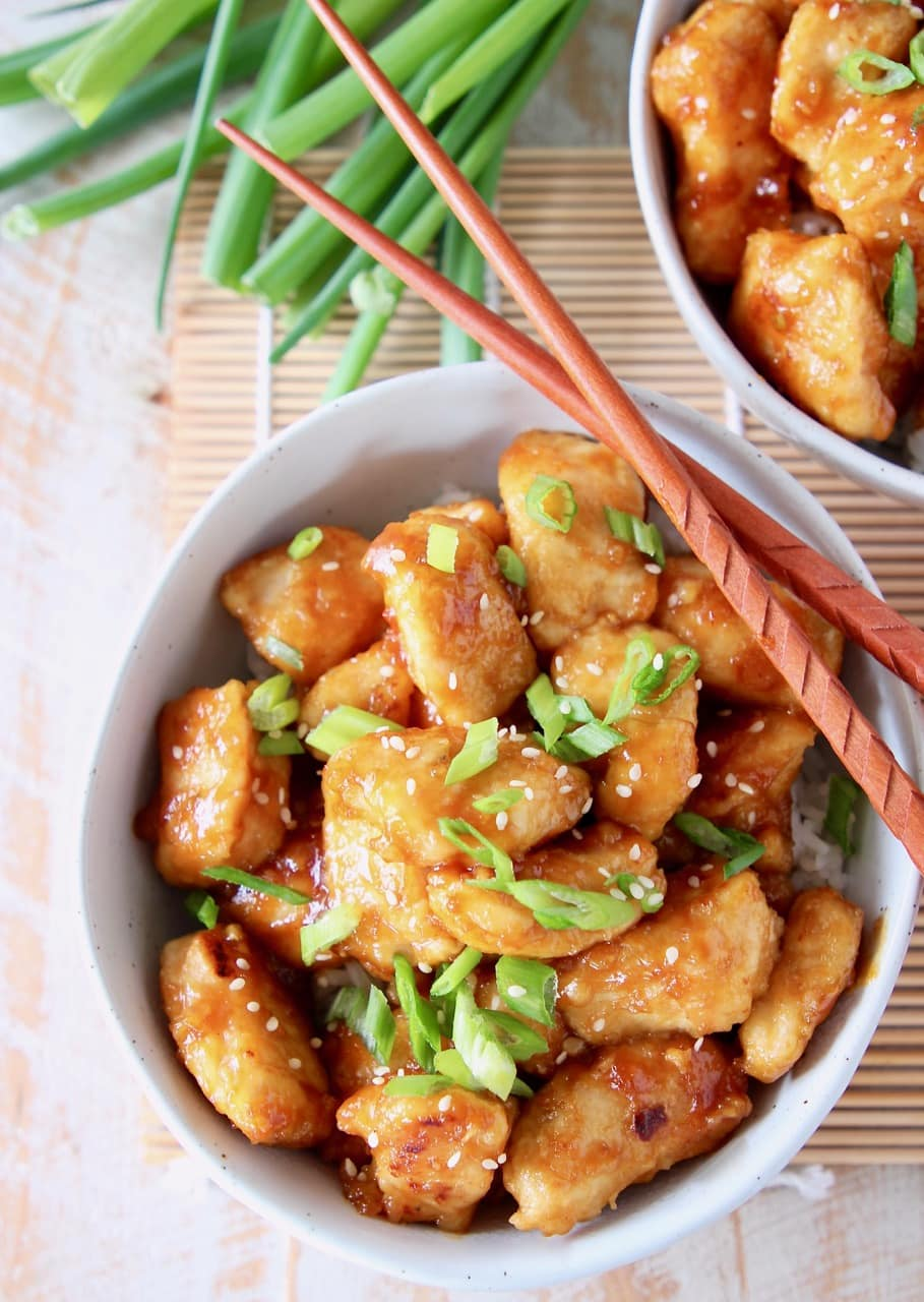 Orange chicken in bowl with diced scallions and wood chopsticks