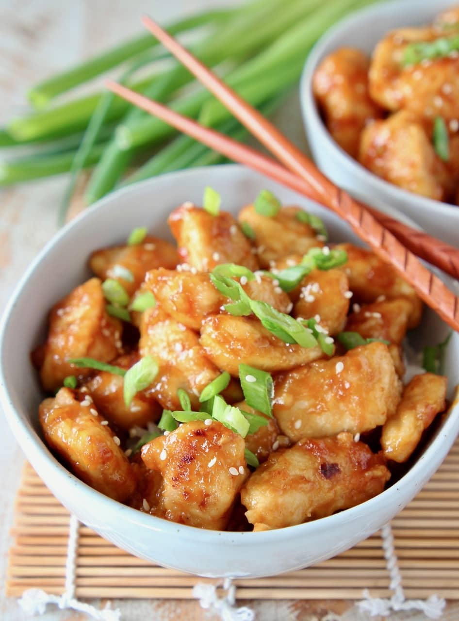 Orange chicken in bowl topped with sliced scallions and sesame seeds, with wood chopsticks on the side of the bowl
