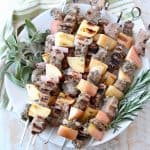 Pork and apple skewers on plate with fresh herbs