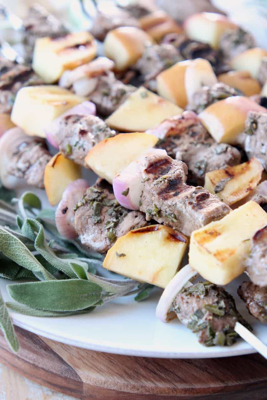 Pork and apple skewers on plate with fresh sage