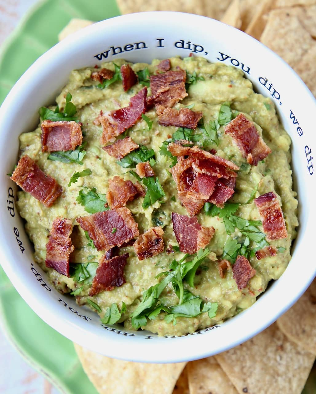 Guacamole in white bowl with crumbled cooked bacon on top