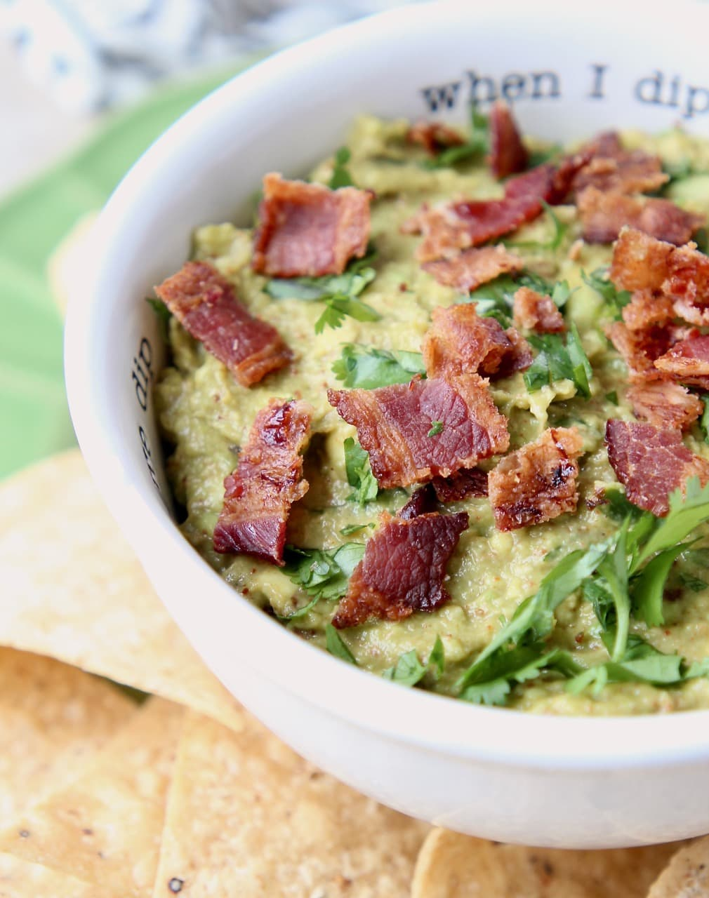 Guacamole in white bowl topped with diced cooked bacon pieces and fresh cilantro