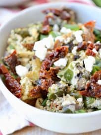 Greek eggs in bowl with feta cheese, sun dried tomatoes and green onions
