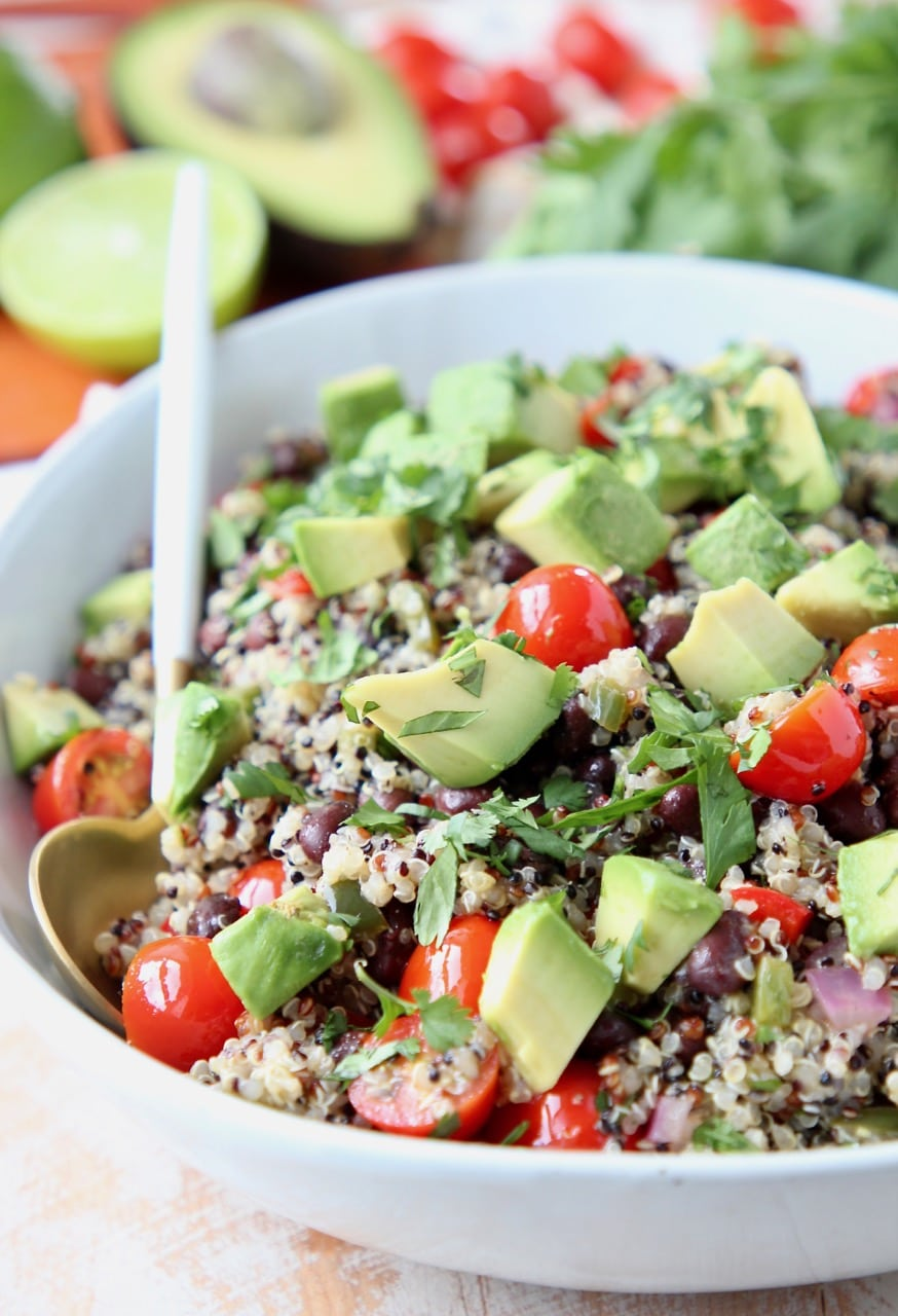 Mexican quinoa salad in bowl with white and gold spoon, topped with diced avocado