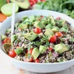 White bowl filled with quinoa salad with diced avocado and tomatoes