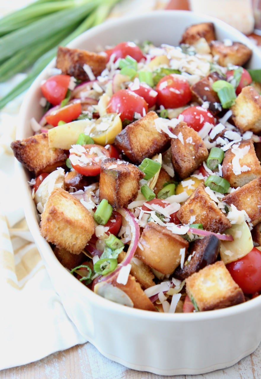 Panzanella salad in bowl with toasted bread pieces and halved cherry tomatoes, topped with grated parmesan cheese