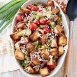 Overhead shot of panzanella salad in large oval bowl topped with grated parmesan cheese