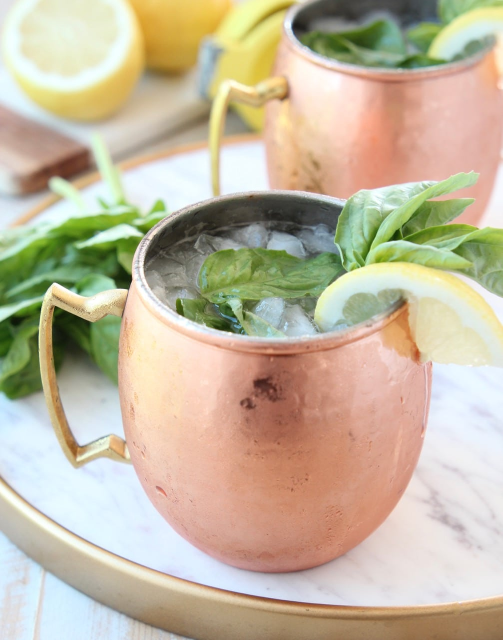 Copper mug filled with ice, vodka and ginger beer, on marble tray
