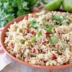 Mexican rice with tomatoes, topped with fresh cilantro in orange bowl