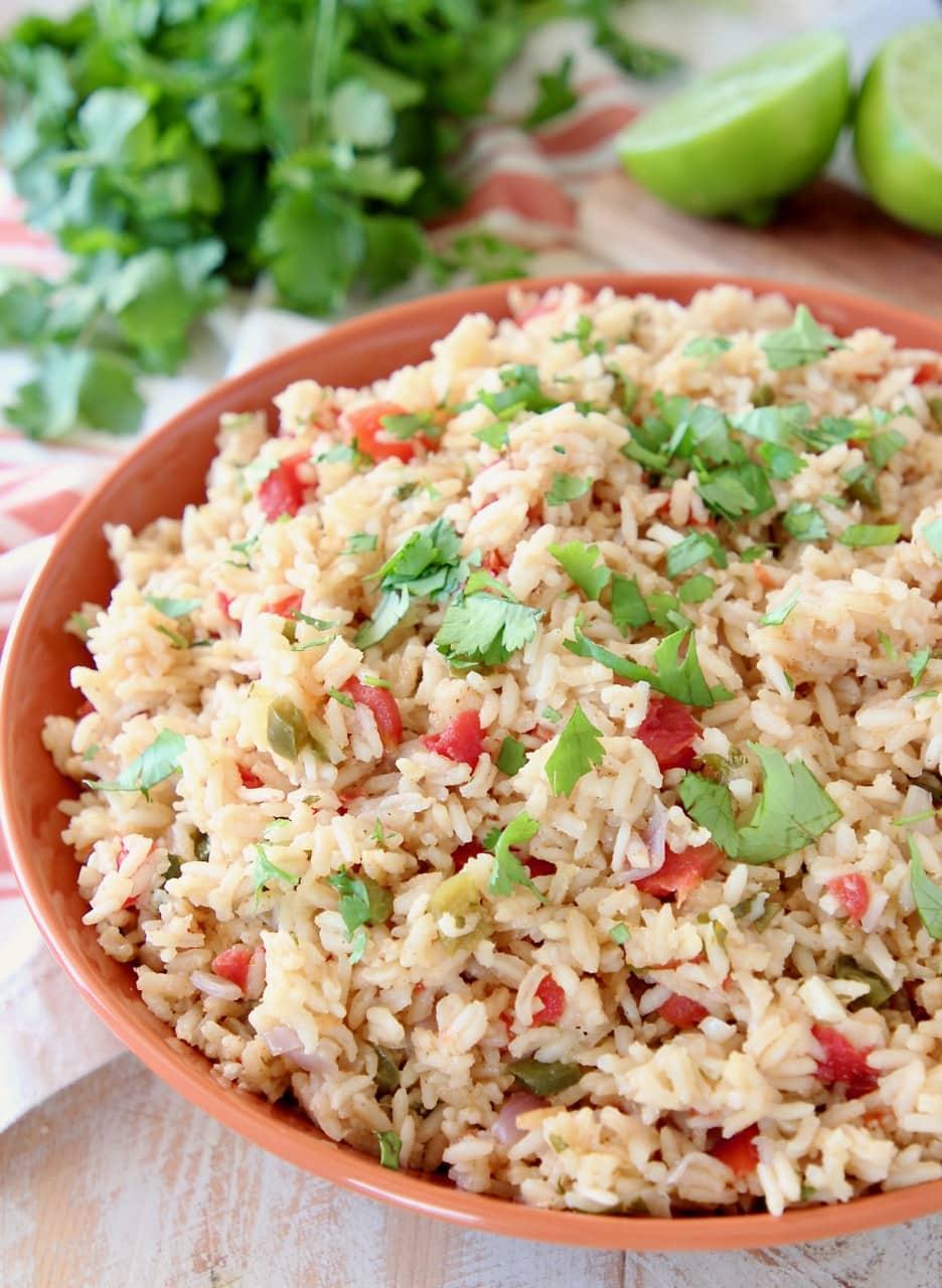 Mexican rice with fresh cilantro in orange bowl