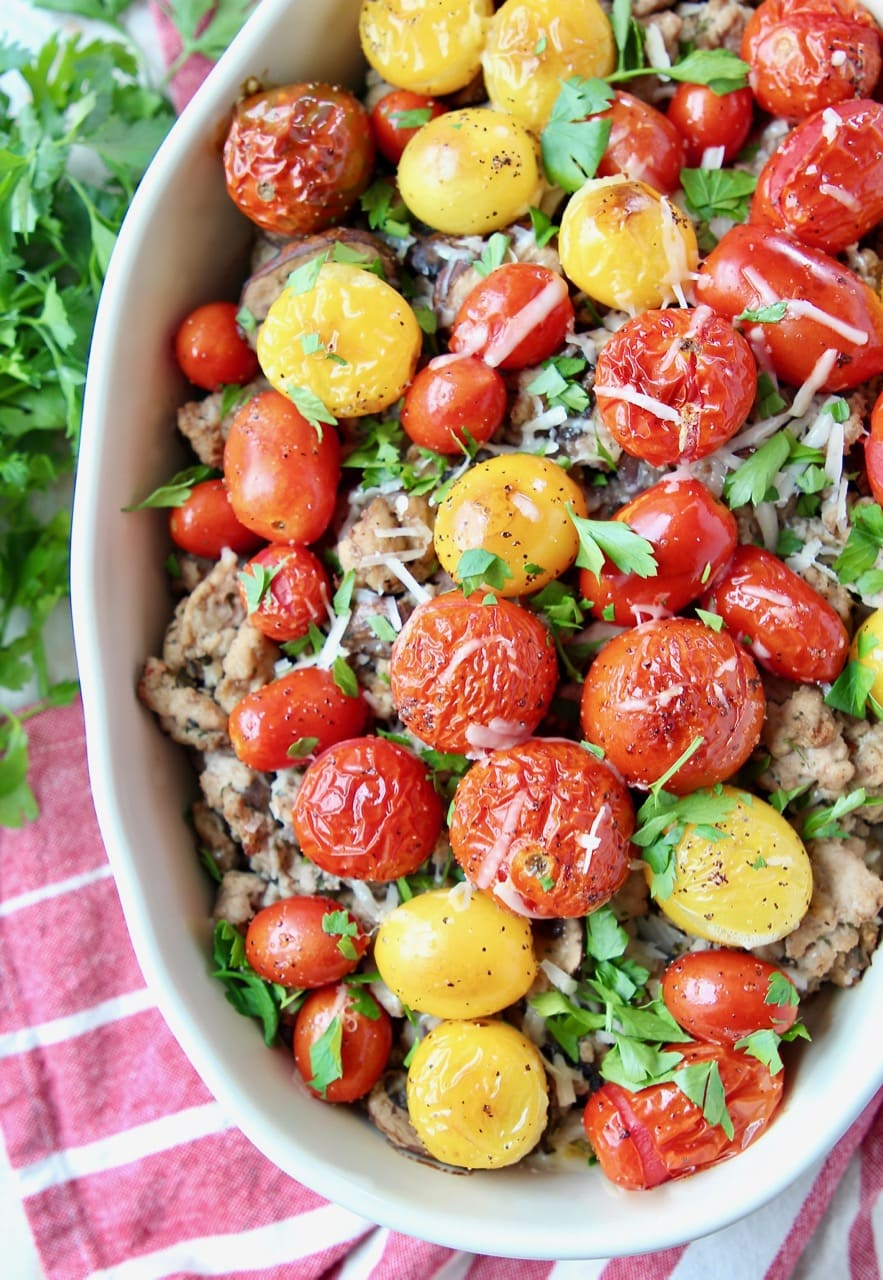 Casserole dish filled with Italian ground turkey, roasted cherry tomatoes and chopped parsley