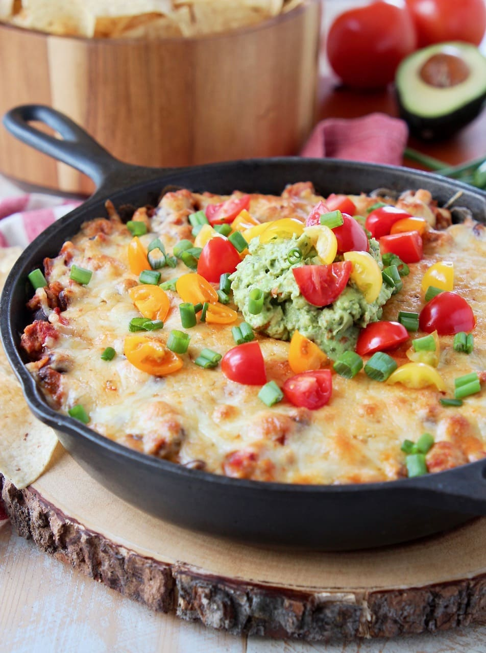 Baked taco dip in a cast iron skillet, sitting on a wood cutting board with a bowl of chips in the background, sitting on a red and white striped towel