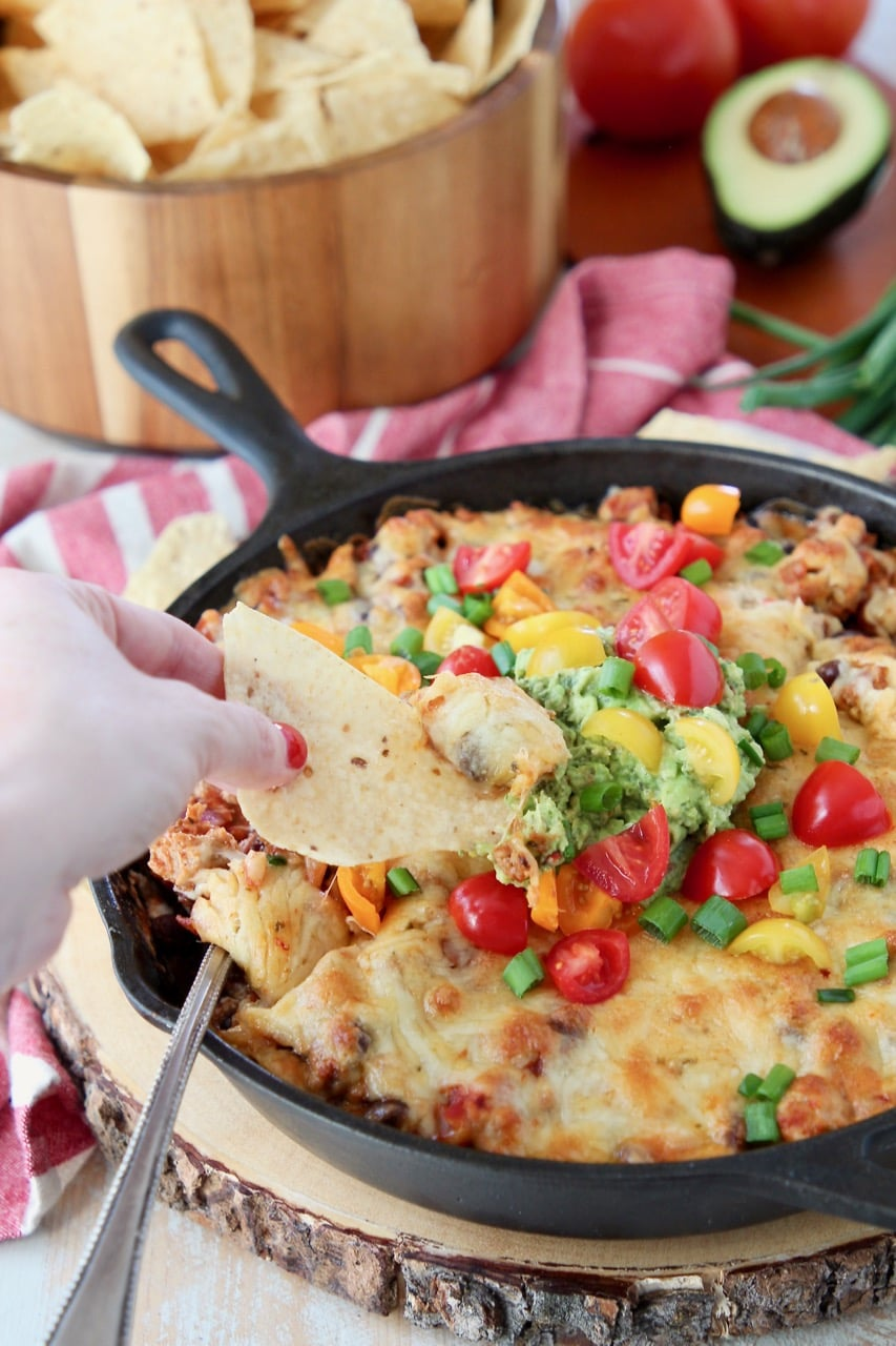 Hand dipping chip into cheesy baked taco dip topped with guacamole and diced tomatoes