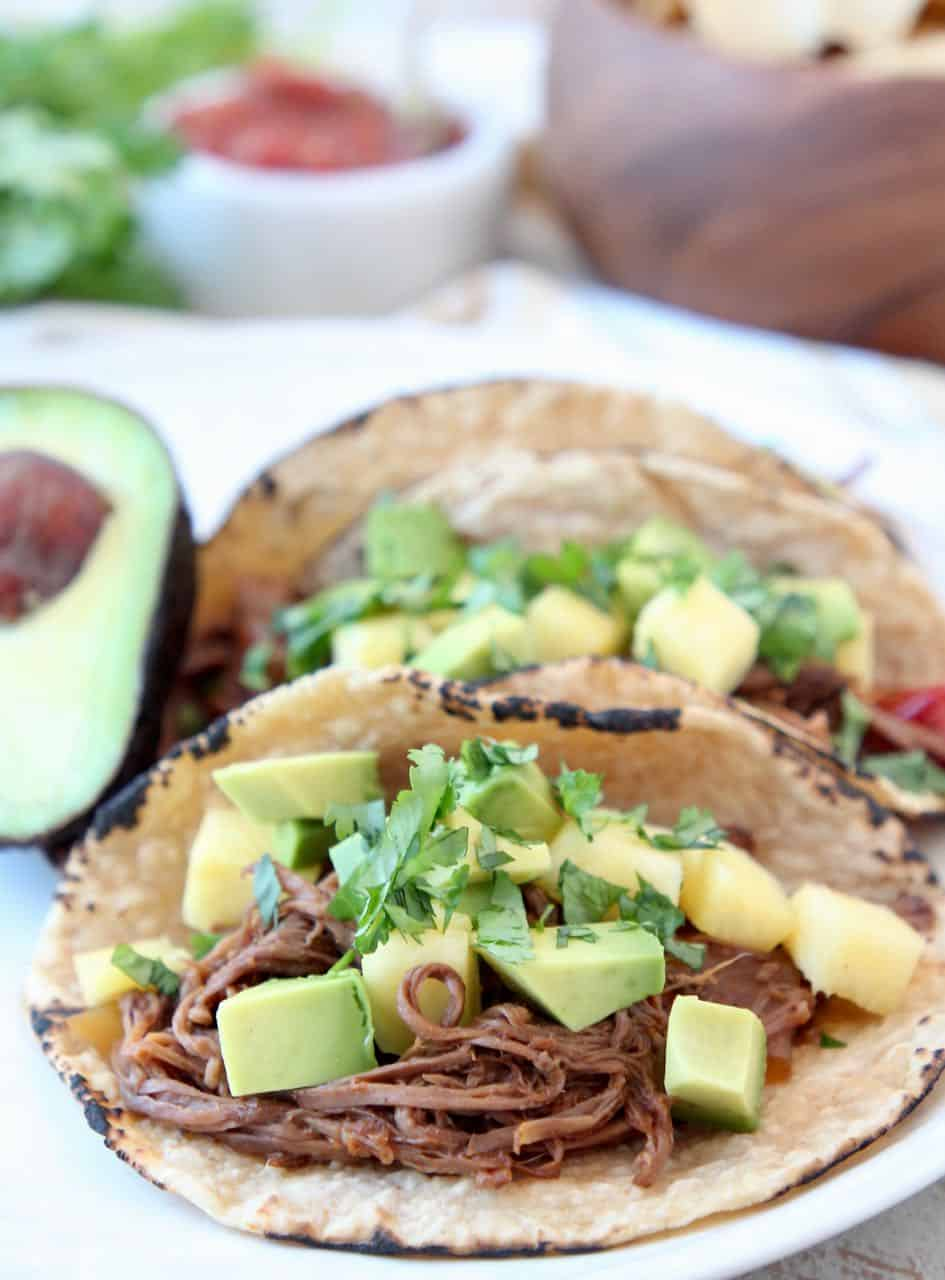 Shredded beef tacos topped with diced pineapple and avocado