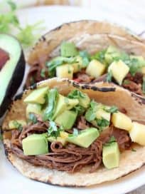 Shredded beef tacos in corn tortillas on plate with avocado and cilantro