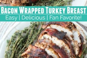 Sliced bacon wrapped turkey breast on plate with fresh herbs