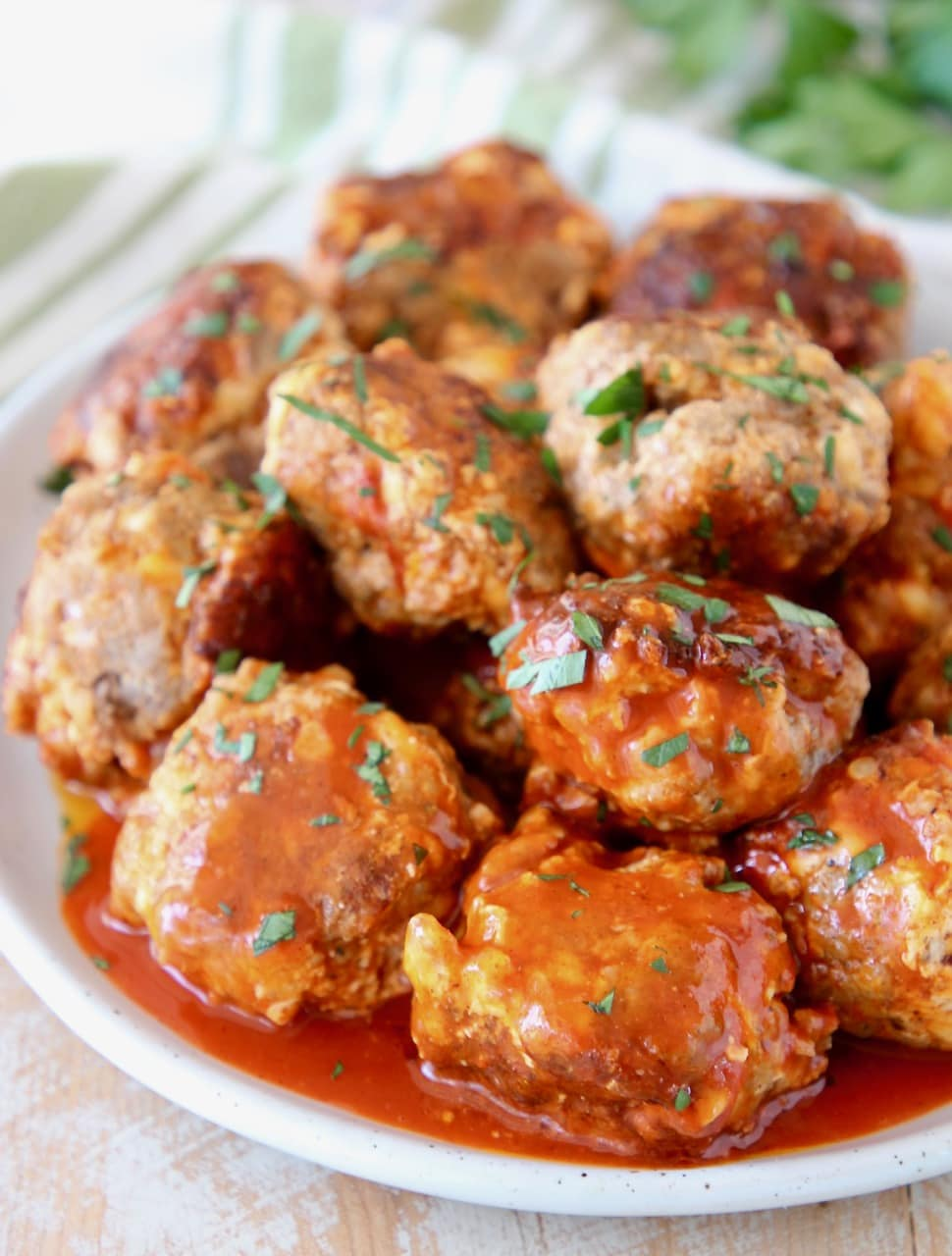 Cheesy Sausage Balls covered in Buffalo Sauce with Fresh Cilantro