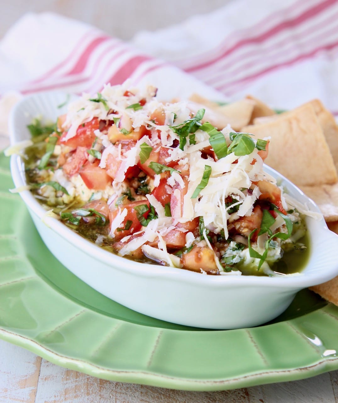 Italian 5 Layer Dip in white oval serving dish, on top of green plate with pita chips and red and white striped towel in background