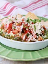 Italian 5 layer dip topped with tomato basil bruschetta in a white serving bowl sitting on a green plate with pita chips
