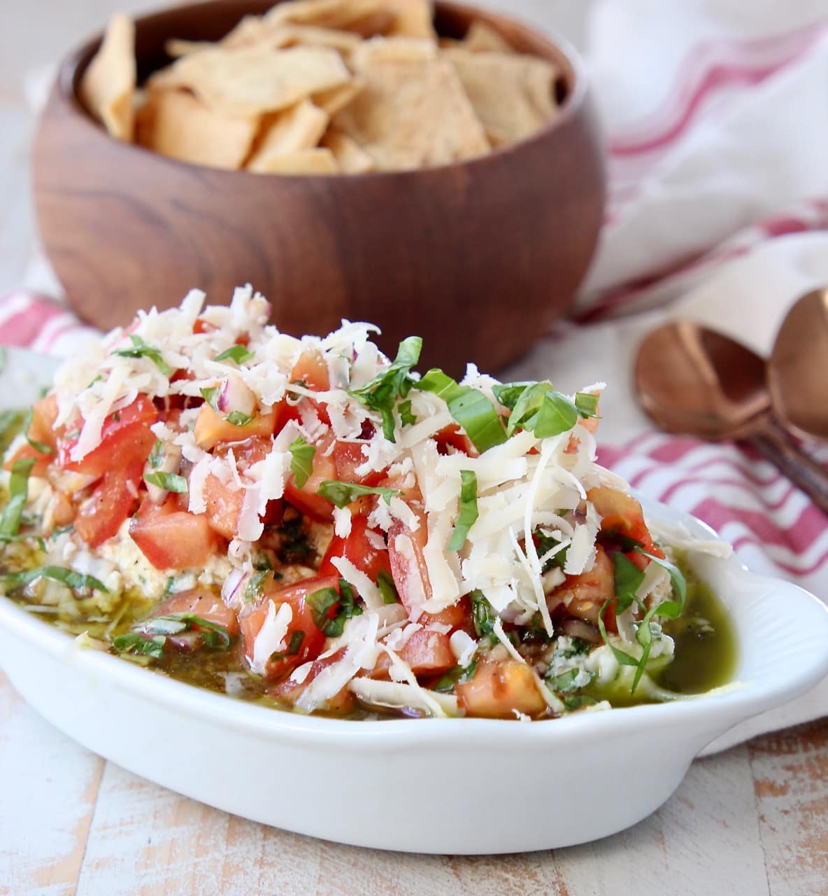 Italian 5 layer dip in white serving bowl with wooden bowl of pita chips behind it and 2 copper spoons next to it