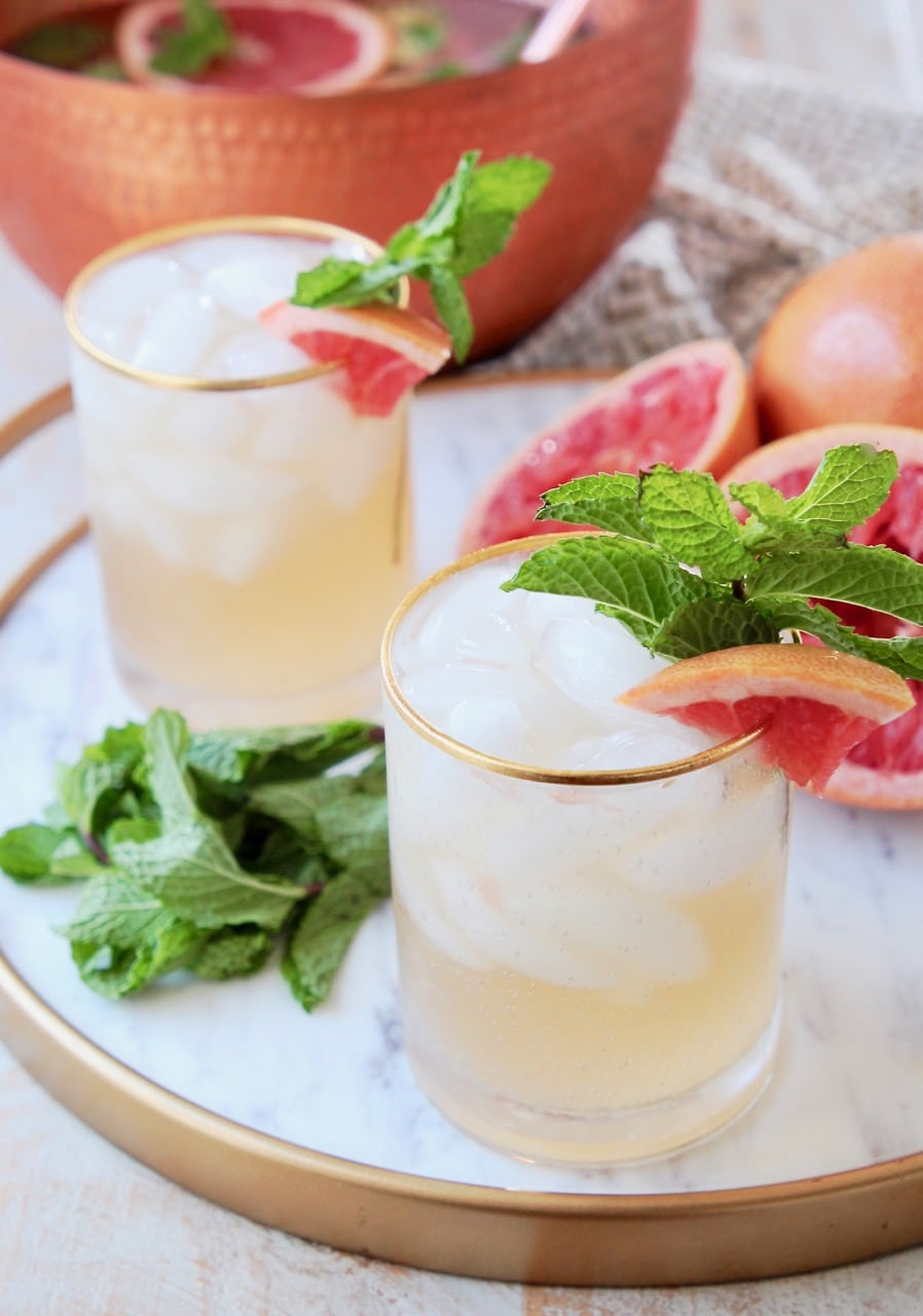 Glasses of spiced rum punch with gold rim, garnished with fresh mint and grapefruit slices, sitting on marble and gold serving tray with fresh mint leaves and squeezed grapefruit halves