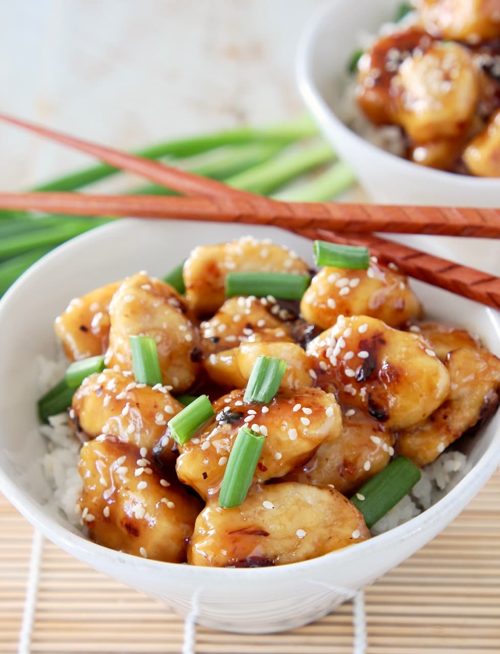 Chinese honey chicken pieces in white bowl with white rice, garnished with green onions and sesame seeds with brown chopsticks on the side of the bowl and whole green onions in the background
