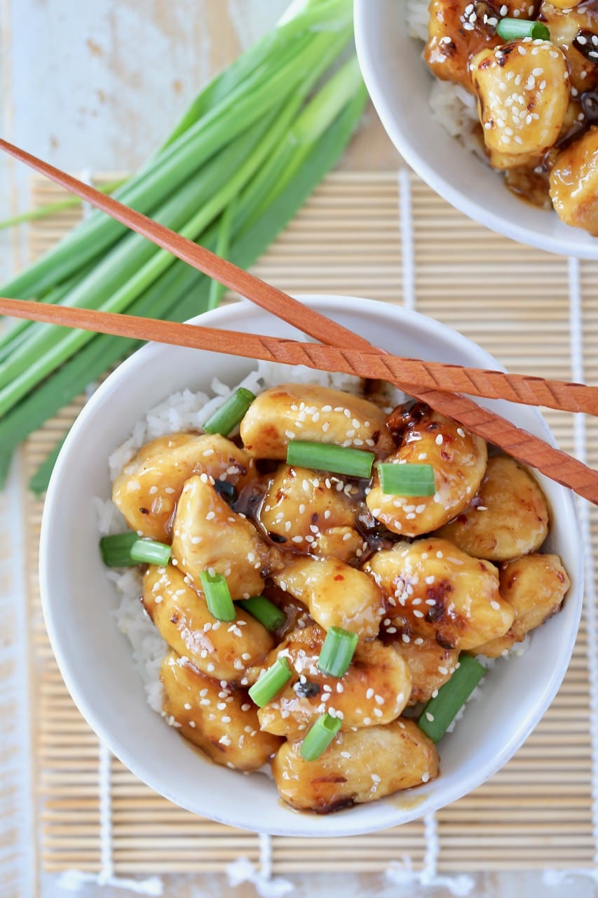 Overhead shot of Chinese honey chicken in white bowl with white rice, green onions and sesame seeds with chopsticks on the side of the bowl and green onions next to the bowl