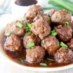 Korean BBQ Meatballs on plate with korean bbq sauce and diced green onions
