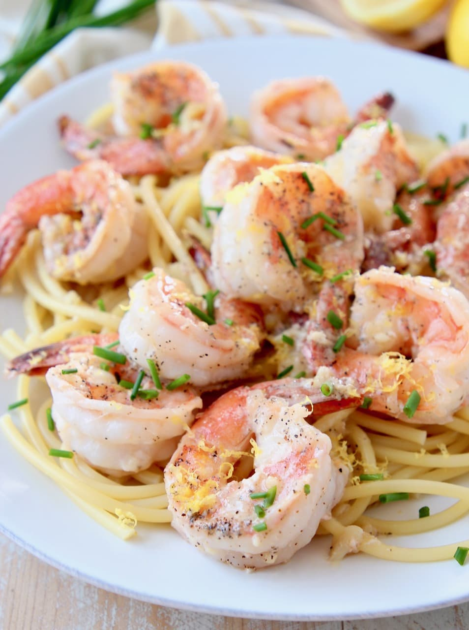 Shrimp over pasta, topped with chives and lemon zest on white plate