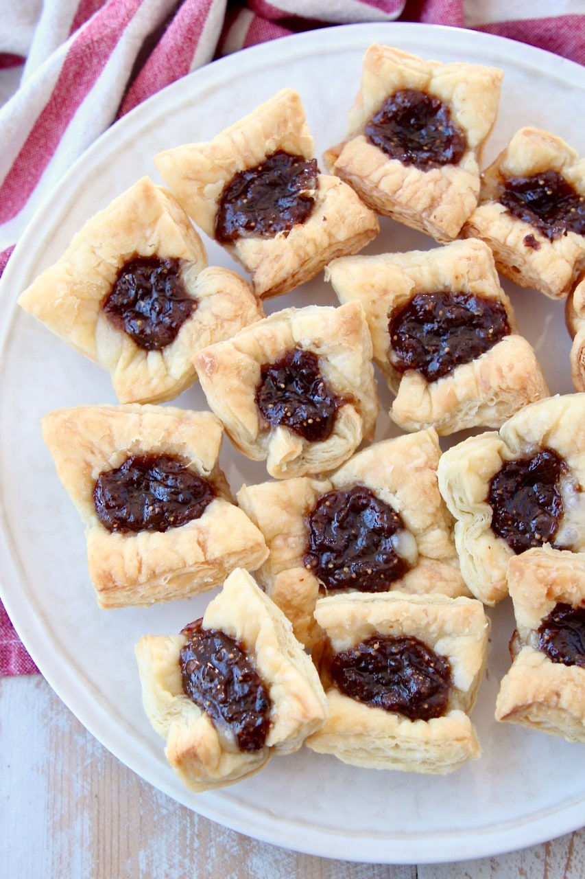 Baked puff pastry bites, filled with brie and jam, sitting on plate