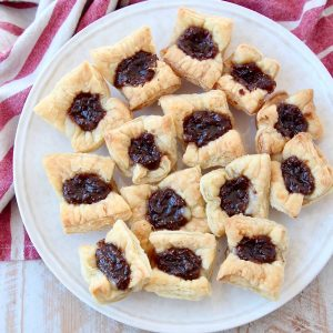 Baked puff pastry bites filled with fig jam on plate